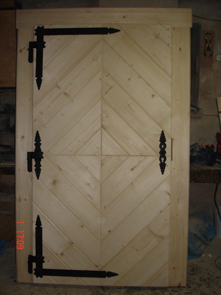 drewniane drzwi wejsciowe zczarnymi okuciami