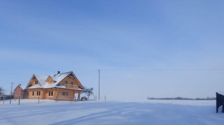 dom drewniany wsniegu-polokragle bale